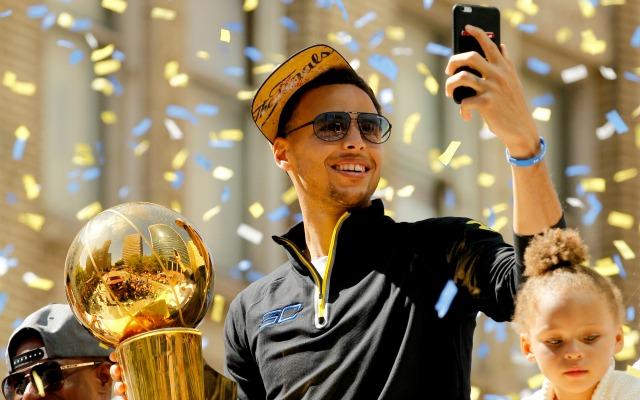 Jun 19, 2015; Oakland, CA, USA; Golden State Warriors guard Stephen Curry takes a photo with his cellular phone during the Golden State Warriors 2015 championship celebration in downtown Oakland. Mandatory Credit: Cary Edmondson-USA TODAY Sports