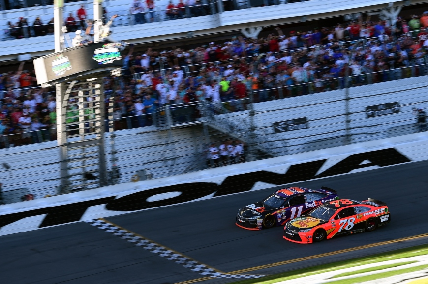 DAYTONA BEACH, FL - FEBRUARY 21:  Denny Hamlin, driver of the #11 FedEx Express Toyota, takes the checkered flag ahead of Martin Truex Jr., driver of the #78 Bass Pro Shops/Tracker Boats Toyota, to win the NASCAR Sprint Cup Series DAYTONA 500 at Daytona International Speedway on February 21, 2016 in Daytona Beach, Florida.  (Photo by Jared C. Tilton/Getty Images)